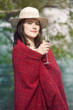Woman wrapped in a red blanket holding a glass of champagne Royalty Free Stock Photography