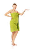 Woman wrapped in towel holding something on palm. Stock Photos