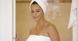 Woman wrapped in towel leaving shower stall Stock Photography