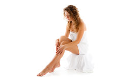 Woman wrapped in towel sitting on white background Stock Photo