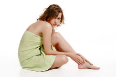 Woman wrapped in a towel. On white background royalty free stock image