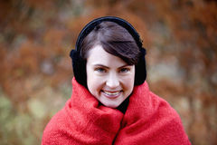A woman wrapped up in a blanket wearing earmuffs Royalty Free Stock Image