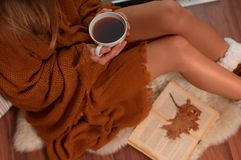 Woman wrapped in a warm plaid blanket drinking hot tea and reading a book in autumn. Beautiful woman wrapped in a warm plaid blanket drinking hot tea and reading Stock Photography