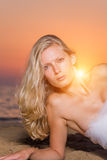 Woman wrapped in wedding veil on the beach. Beautiful young woman wrapped in wedding veil on the beach at sunrise Royalty Free Stock Photos
