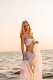 Woman wrapped in wedding veil on the beach Stock Photography