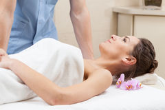 Woman wrapped in white towel lying on massage table Stock Images