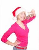 Woman wrapping christmas balls wearing santa ha Stock Photos