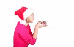 Woman wrapping christmas balls wearing santa ha Royalty Free Stock Image