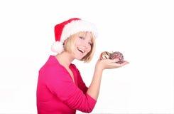 Woman wrapping christmas balls wearing santa ha Stock Photography
