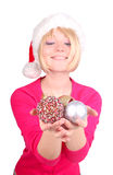 Woman wrapping christmas balls wearing santa ha Stock Photo