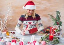 Woman wrapping Christmas present box Stock Photos