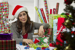 Woman wrapping Christmas presents, looking exhausted. Royalty Free Stock Image