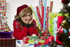 Woman wrapping Christmas presents, looking exhausted. Royalty Free Stock Photos