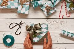 Woman wrapping christmas presents over wooden background royalty free stock image