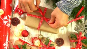 Woman is wrapping Christmas presents on the table, concept of preparing for the New Year and Christmas holidays stock video