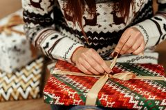 Woman wrapping christmas presents under tree closeup in sweaters. With deers. stylish gift ideas. seasonal greetings concept. joyful moment. space for text royalty free stock photos