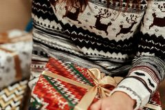 Woman wrapping christmas presents under tree closeup in sweaters. With deers. stylish gift ideas. seasonal greetings concept. joyful moment. space for text royalty free stock images