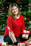 Woman Wrapping and Decorating Christmas Present at Home stock photo