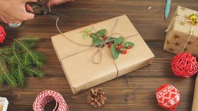 Woman wrapping gift box with decorating items on wood table, close up, top view. stock footage