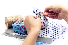 Woman is wrapping a gift with natural materials and organic cotton