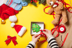 Woman wrapping gingerbread cookie Royalty Free Stock Images