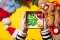 Woman wrapping gingerbread cookie Stock Photography