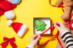 Woman wrapping gingerbread cookie Royalty Free Stock Image