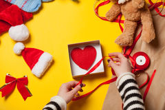 Woman wrapping a heart shape toy Stock Photo