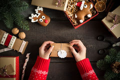 Woman wrapping modern Christmas presents with blank gift tag on old wooden background. Eye bird view. Royalty Free Stock Photo