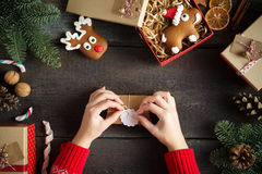 Woman wrapping modern Christmas presents with blank gift tag on old wooden background. Eye bird view. Stock Photography
