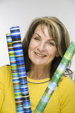 Woman with wrapping paper. Waist up a woman middle age, yellow sweatshirt and colorful roll wrapping paper before light Studio background royalty free stock image
