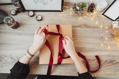 Woman wrapping present in paper with red ribbon. stock photography