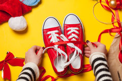 Woman wrapping red gumshoes Stock Photography
