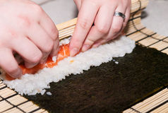 Woman wrapping rice and salmon to sushi roll Royalty Free Stock Photo