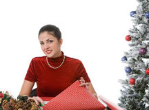 Woman wraps Christmas gifts. Woman wrapping Christmas gifts in a Christmas setting against a white background Stock Photography