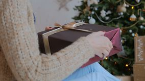 Woman wraps ribbon on christmas gift box. At home. Holidays, x-mas and new year concept stock footage
