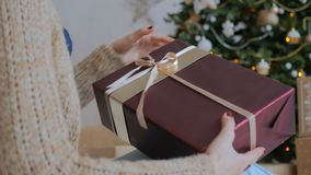 Woman wraps ribbon on christmas gift box. At home. Holidays, x-mas and new year concept stock video