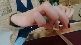 Woman wraps ribbon on christmas gift box. At home. Point of view - POV - shot. Holidays, x-mas and new year concept stock video