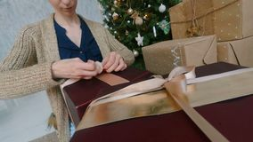 Woman wraps ribbon on christmas gift box. At home. Point of view - POV - shot. Holidays, x-mas and new year concept stock video footage