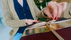 Woman wraps ribbon on christmas gift box. At home. Point of view - POV - shot. Holidays, x-mas and new year concept stock photography
