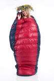 Woman With The Wreast In The Sleeping Bag. Young blonde woman with the wraest on her head in the down sleeping bag stock image