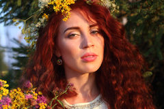 Woman in wreath with bunch of flowers at summer, close Stock Photos