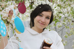 Woman with wreath and Easter cake among spring garden Royalty Free Stock Images