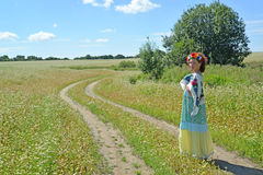 The woman with a wreath on the head goes on a path in the blosso Stock Images