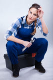 Woman with a wrench. Woman holding a wrench and sitting on her toolbox Stock Photo