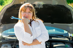 Woman with a wrench near the open hood Stock Images