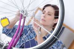 Woman with wrench repairs bicycle Stock Images