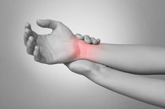 Woman with wrist pain. A young woman touching her painful wrist stock image