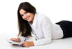 Woman writ in notepad laying on the floor Stock Image
