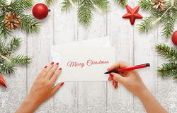 Woman write Christmas greeting card. Christmas tree with decorations beside royalty free stock images